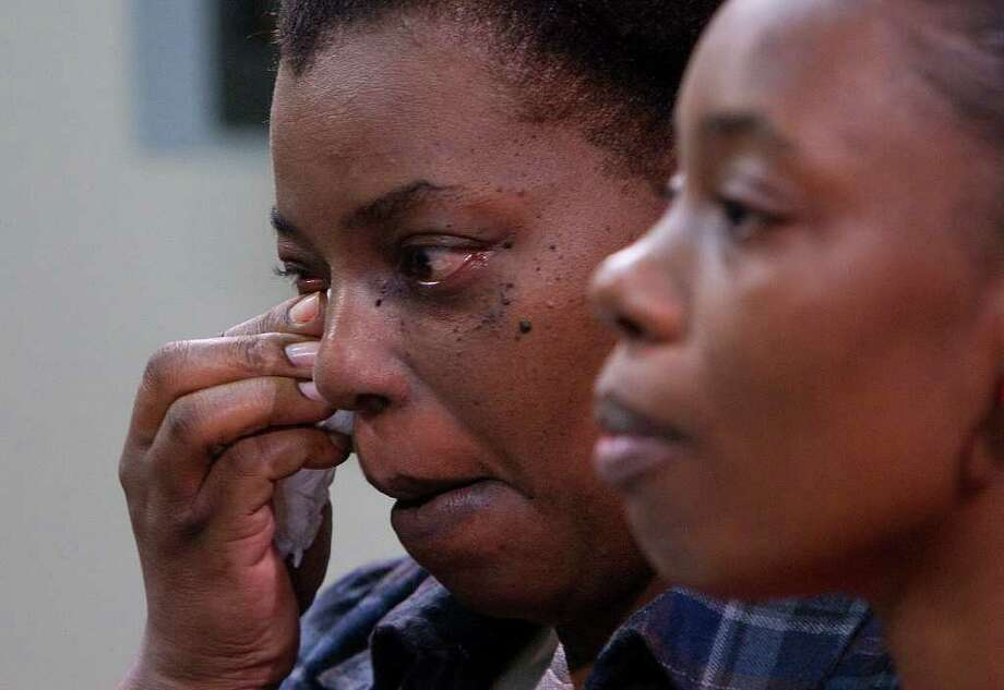 Angela Potter, left, wipes her eyes as she stands with her sister, April St. Jules, right, as they attend a press conference at Crime Stoppers Wednesday, Nov. 16, 2011, in Houston regarding the unsolved killing of their brother, Afernee Williams. Photo: Cody Duty / © 2011 Houston Chronicle