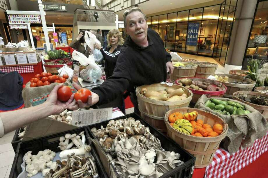 Russell Madura offers organic tomatoes from Madura Farms market during the opening day of the Indoor Winter Farmers Market at the Danbury Fair mall Saturday, Nov. 12, 2011. Photo: Michael Duffy / The News-Times