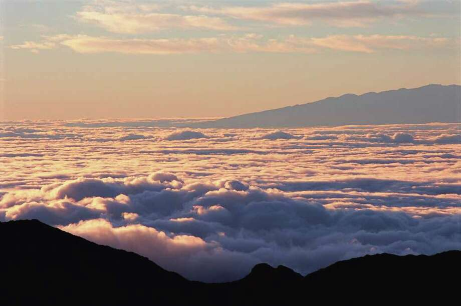The sea of clouds reflects the drama of subtle shadows and light during sunrise at Haleakala National Park. / handout