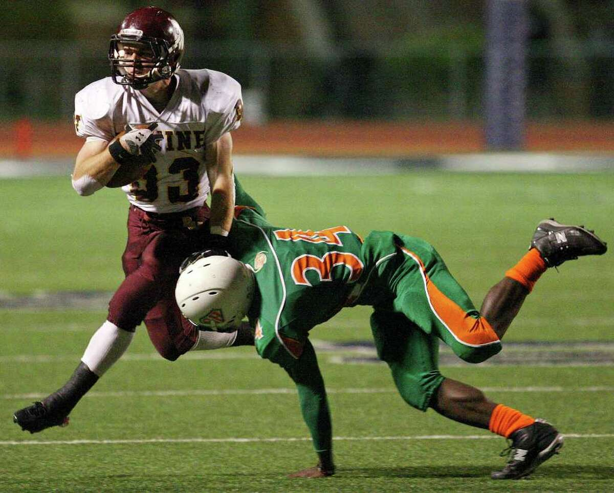FOR SPORTS - Devine's Joseph Sadler looks for room around Sam Houston's Tomaria Stringfellow during first half action of their Class 3A-Division II bi-district playoff game Friday Nov. 11, 2011 at South San Stadium. (PHOTO BY EDWARD A. ORNELAS/eaornelas@express-news.net)