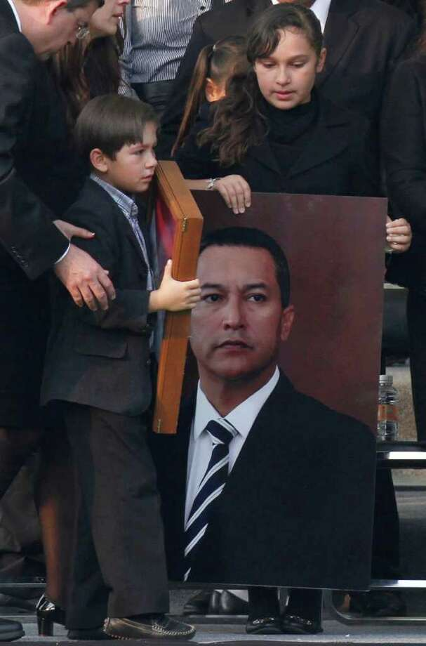 ASSOCIATED PRESS TRAGIC LOSS: Gloria and Jose Francisco Blake Cossio, daughter and son of late Mexican Interior Minister Jose Francisco Blake Mora, attend their father's funeral Saturday. Photo: Marco Ugarte / AP