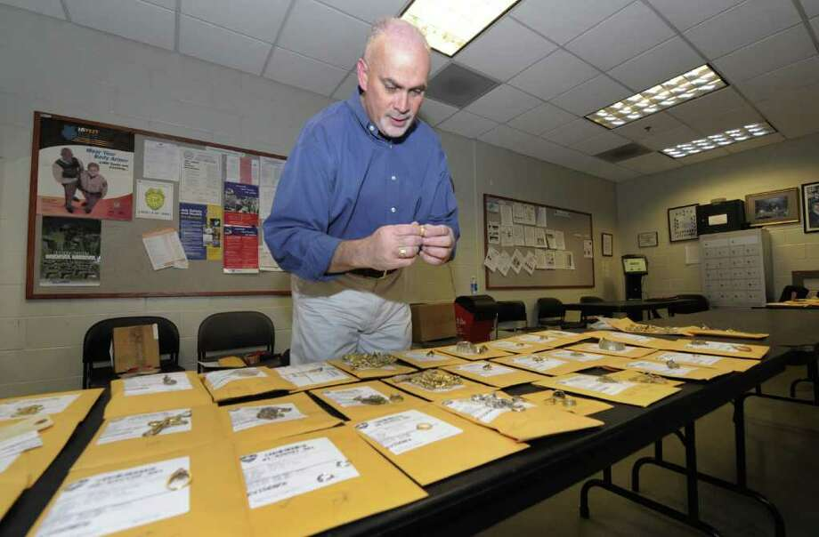 Bill Chamberlain, Director of Operations for the City of Troy looks over some of the numerous pieces of jewelry that were confiscated as part of investigations by the Troy Police Department and remained unclaimed and were auctioned off today Nov. 16, 2011 at the Troy, N.Y. Police Station. (Skip Dickstein/Times Union) Photo: Skip Dickstein / 00015388A