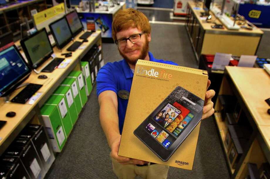 Cody Duty : Chronicle FIRE IN HIS HANDS: The newest version of the Kindle went on sale this week at stores including the Galleria-area Best Buy, where Matt Ford works. The Android-based tablet computer goes for just under $200. Photo: Cody Duty / © 2011 Houston Chronicle