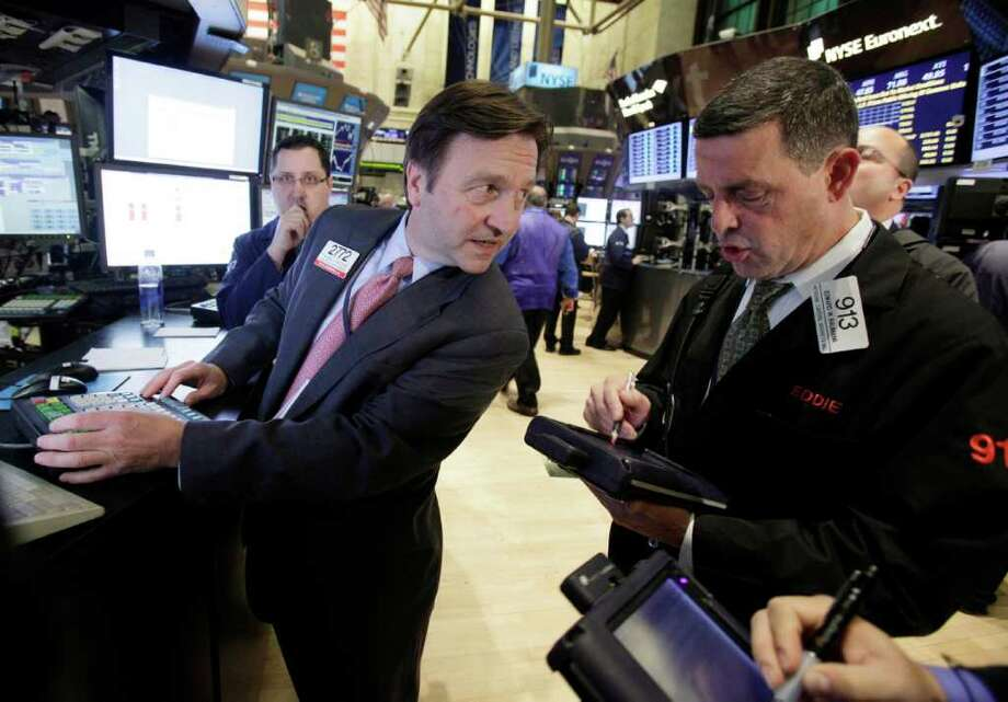 In this Nov. 9, 2011 photo, specialist Thomas Facchine, left, and trader Edward Baumann work on the floor of the New York Stock Exchange. Continuing unease over Europe's debt crisis pushed investors out of global stock markets Wednesday, Nov. 16, 2011, even though pressure on the interest rates European countries pay to borrow money eased after skyrocketing a day earlier. (AP Photo/Richard Drew) Photo: Richard Drew