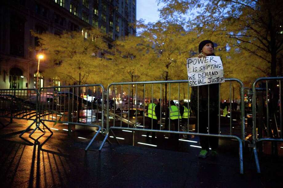 A solitary Occupy Wall Street protestor holds a sign outside a nearly empty Zuccotti Park during the early morning hours, Wednesday, Nov. 16, 2011, in New York. Crackdowns against the Occupy Wall Street encampments across the country reached the epicenter of the movement Tuesday, when police rousted protesters from the park and a judge ruled that their free speech rights do not extend to pitching a tent and setting up camp for months at a time. (AP Photo/John Minchillo) Photo: John Minchillo