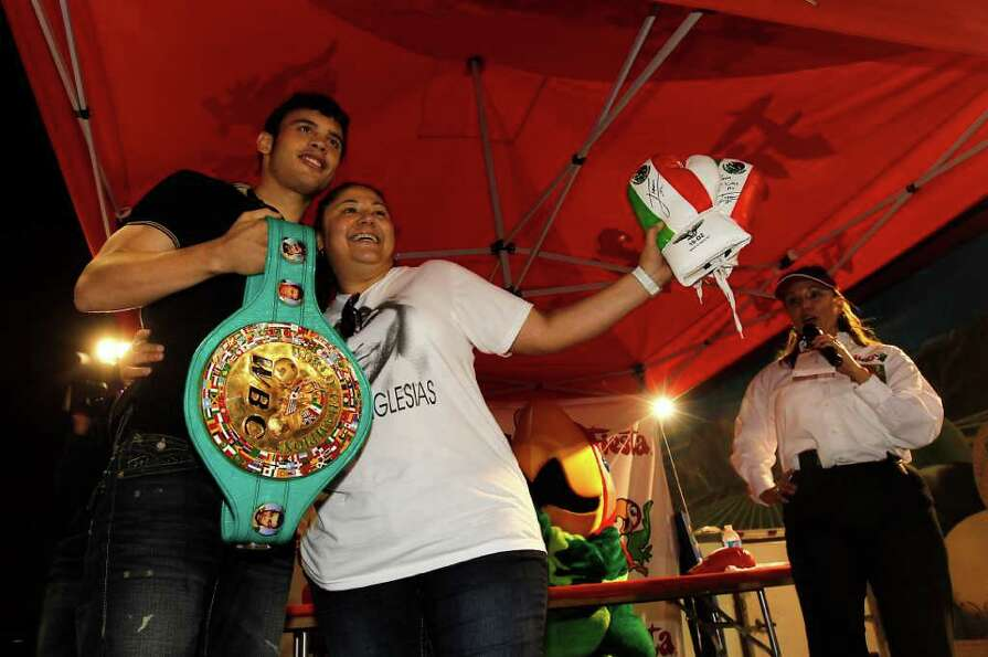 Olga Cantu, who was the first person in line,  gets her photo taken with boxer Julio Cesar Chavez, J