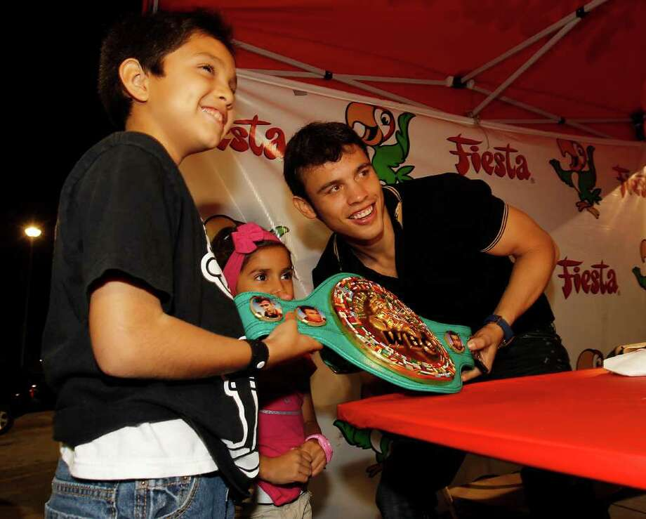Boxer Julio Cesar Chavez, Jr. takes a photo with Mia Avendano, 5, center and Mauricio Ramirez, 9, as he signed autographs at the Fiesta, 4711 Airline, Nov. 16, 2011. Chavez, Jr. (43-0-1, 30KOs) will face Peter Manfredo, Jr. (37-6, 20KOs) this Saturday, November 19th in Houston, Texas. Chavez, Jr. is currently ranked the 6th best middleweight in the world by The Boxing Tribune and holds the divisionÕs WBC title belt. Photo: Karen Warren, Houston Chronicle / © 2011 Houston Chronicle