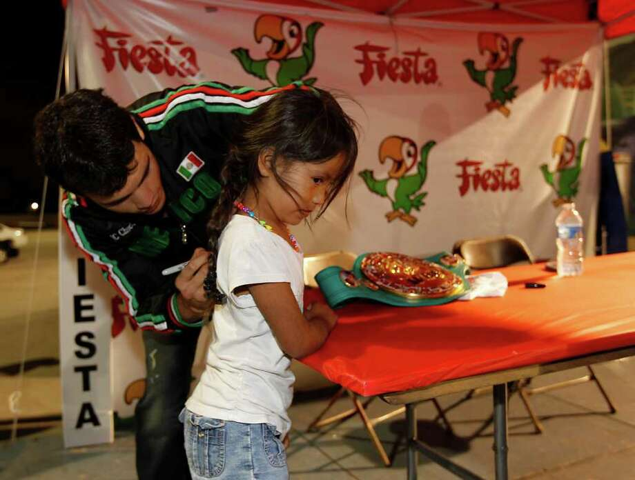 Boxer Julio Cesar Chavez, Jr. signs six-year-old, Natalia Saavedraa's shirt as he signs autographs at the Fiesta, Nov. 16, 2011. Photo: Karen Warren, Houston Chronicle / © 2011 Houston Chronicle