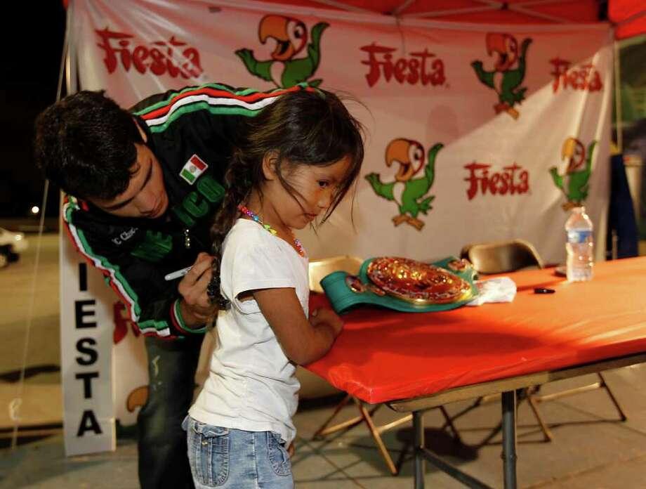 Boxer Julio Cesar Chavez, Jr. signs six-year-old, Natalia Saavedraa's shirt as he signs autographs at the Fiesta, Nov. 16, 2011. Photo: Karen Warren, Houston Chronicle / © 2011 Houston Chronicle