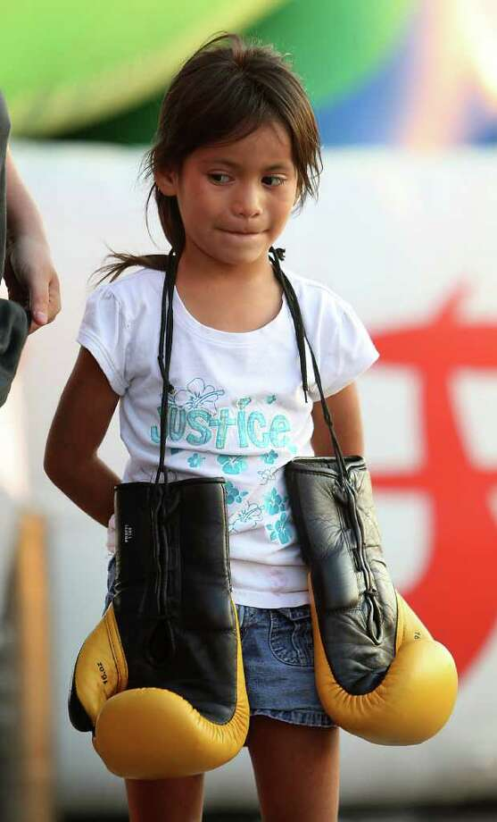 Six-year-old, Natalia Saavedraa holds her cousin's boxing gloves while they wait for the arrival of Julio Chavez, Jr. who signed autographs at the Fiesta, Nov. 16, 2011. Photo: Karen Warren, Houston Chronicle / © 2011 Houston Chronicle