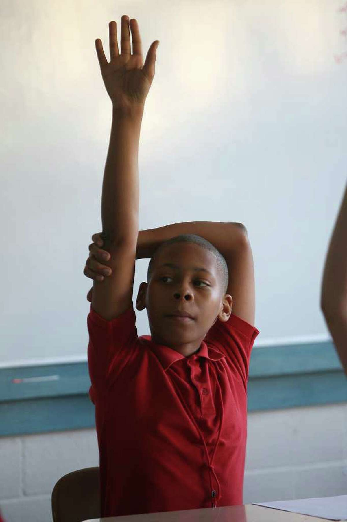 Sixth-grader Brandon Ricard raises his hand Wednesday during a magnet pilot math class at Black Middle School, one of 114 HISD programs with the