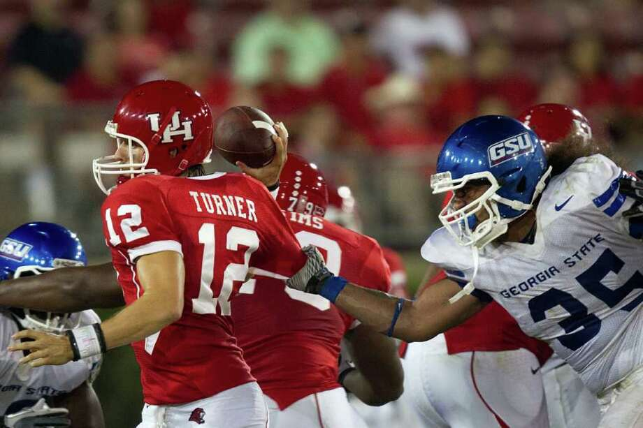 Houston Cougars quarterback Cotton Turner (12) gets off a pass despite the defense of Georgia State Panthers linebacker Jake Muasau (35) during the fourth quarter of an NCAA football game at Robertson Stadium, Saturday, Sept. 24, 2011, in Houston. Houston won the game 56-0. Photo: Smiley N. Pool, Houston Chronicle / © 2011  Houston Chronicle