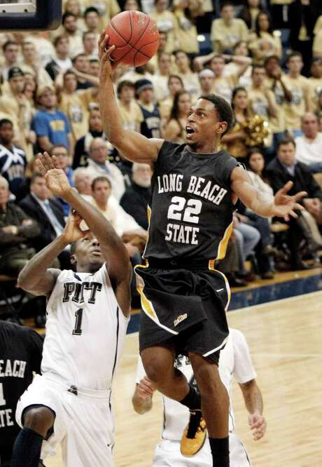 Long Beach State's Casper Ware soars over Pittsburgh's Tray Woodall to score two of his career-high 28 points. Photo: AP