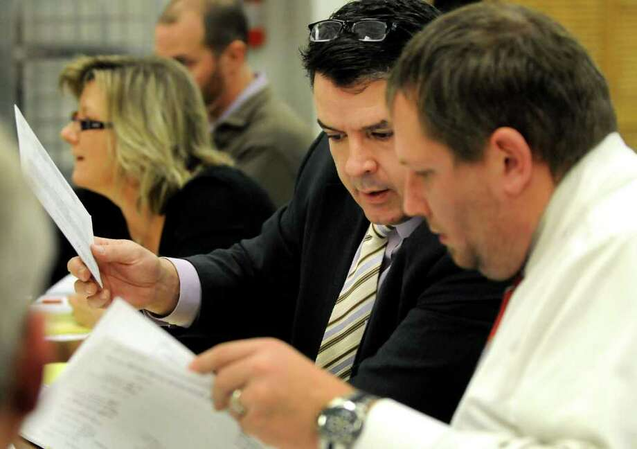 James Walsh, attorney for Roger Hull, center, consults Brian Young, Hull's campaign manager, as they review ballots during a recount for the mayoral race on Wednesday, Nov. 16, 2011, at Schenectady County Board of Elections in Schenectady, N.Y.(Cindy Schultz / Times Union) Photo: Cindy Schultz /  00015405A