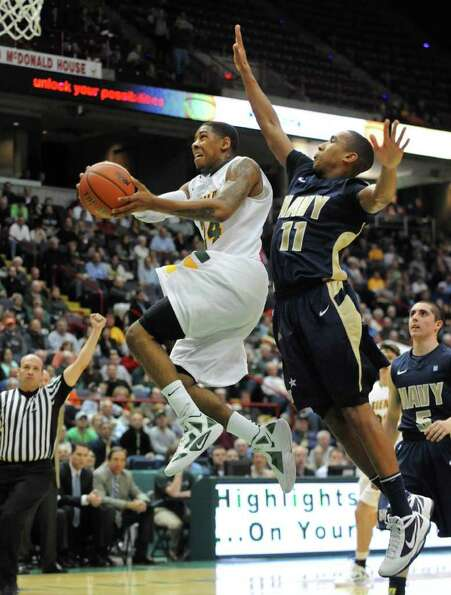 Siena's Davonte Beard is guarded byThurgood Wynn of Navy as he drives to the basket during a basketb