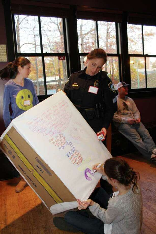Darien Police Officer Keri Isaac watches as Katie Martin decorates a donation box for the Cops & Kids Adventures group's upcoming charity drive. Photo: Contributed Photo
