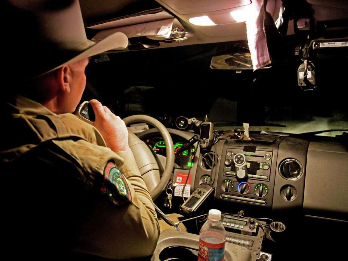 Guadalupe County game warden Kevin Frazier talks on the radio in his pickup as he leaves a ranch while on patrol.