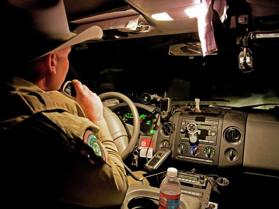 Guadalupe County game warden Kevin Frazier talks on the radio in his pickup as he leaves a ranch while on patrol. Photo: JOHN GOODSPEED/SPECIAL TO TH E-N