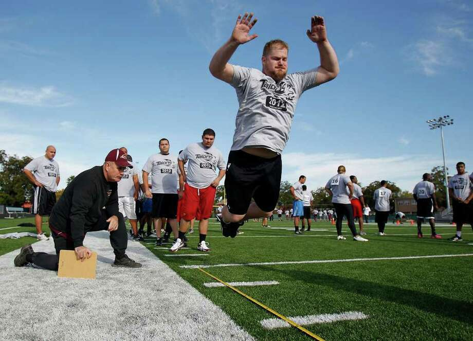 Erick Harris completes a standing broad jump for 6 feet 10.5 inches during San Antonio Talons Arena Football League tryouts at Central Catholic's Benson Stadium on Saturday, Nov. 5, 2011. Harris is trying out for an offensive line position. Photo: Express-News, MICHAEL MILLER / mmiller@express-news.net