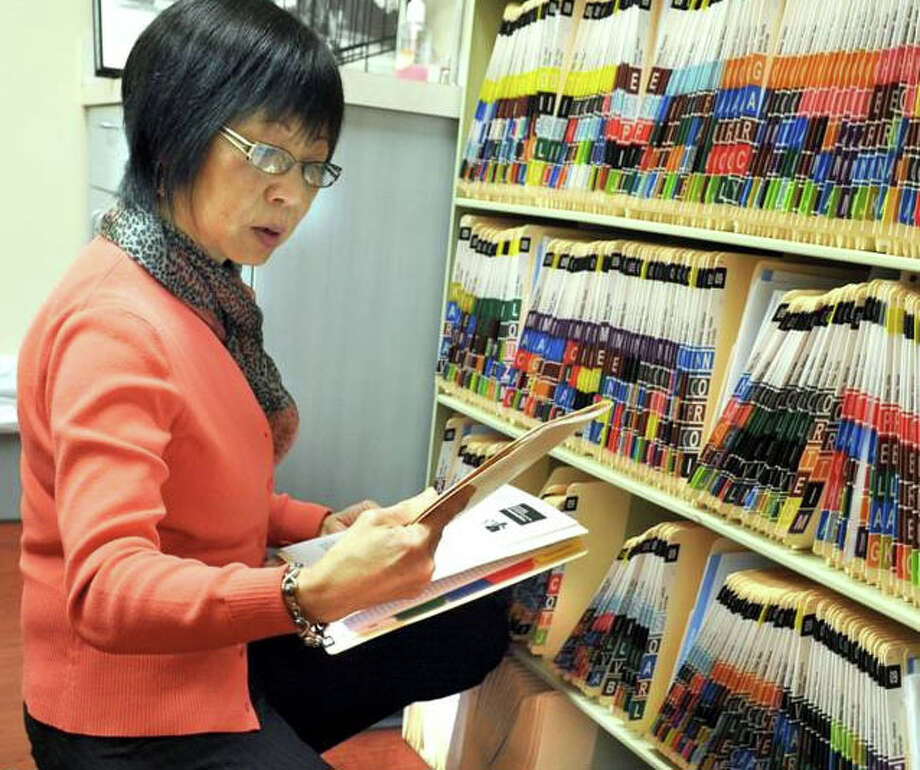 Eva Tan, executive director of the Samaritan Health Center in Danbury, looks through patient files. The health center will be able to switch over to electronic files with help from Walnut Hill Community Church in Bethel. Photo: Carol Kaliff