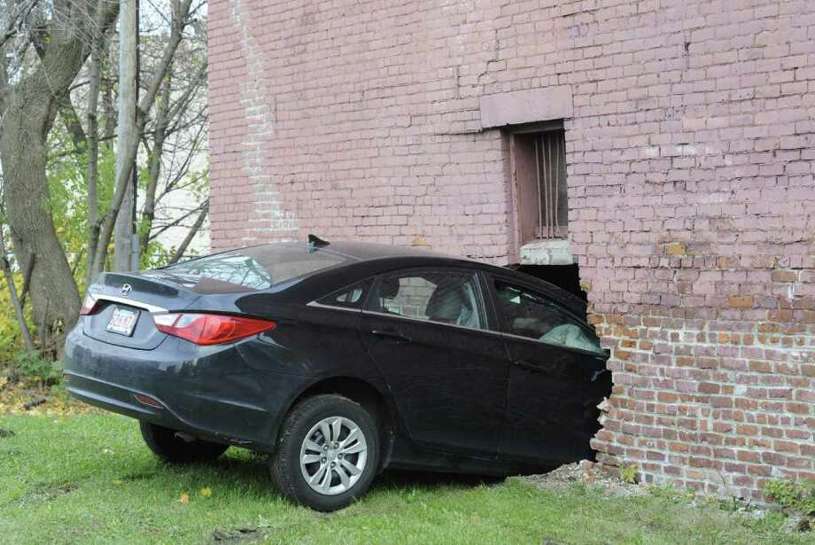 A car sticks out of the side of a house at the intersection of Alexander and Broad streets in Albany, N.Y. Nov. 17, 2011.  (Skip Dickstein/Times Union) Photo: Skip Dickstein / 2011