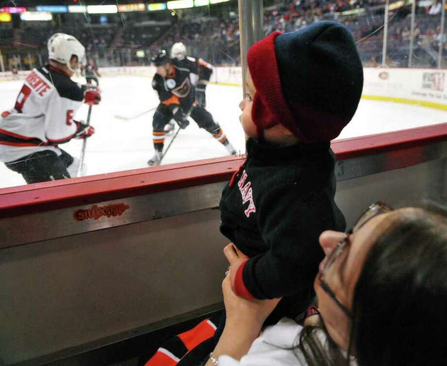 Life-long hockey fan at one-year-old, Jace Sutton of Ballston Lake watches Glens Fall Phantoms and Albany Devils's play from his grandmother, Maria Maloney lap during Saturday night's game at the Times Union Center  Oct. 21, 2011.  (John Carl D'Annibale / Times Union)P Photo: John Carl D'Annibale / 00014829F