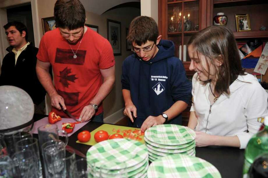 From left, Joshua Genn, Graham Perry, Samuel Savitz and Julia Jandrisits, members of Greenwich High School's Israel Club, cook an Israeli dinner Thursday, Nov. 18, 2011. Twelve members of the club, including the four here, were named recipients of the Weitzman Youth Award for Jewish Philanthropy. Photo: Helen Neafsey / Greenwich Time