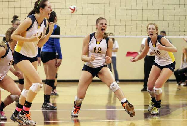 Poth's Kelsee Felux (14), Jordan Kotara (12) and Avery Acker (10) rejoice after winning a point against Jewett Leon in 2A State semifinal volleyball in Strahan Coliseum at Texas State University in San Marcos on Thursday, Nov. 17, 2011. Poth defeated Leon in four games to move onto the state finals to be played on Saturday. Photo: Kin Man Hui, ~ / San Antonio Express-News