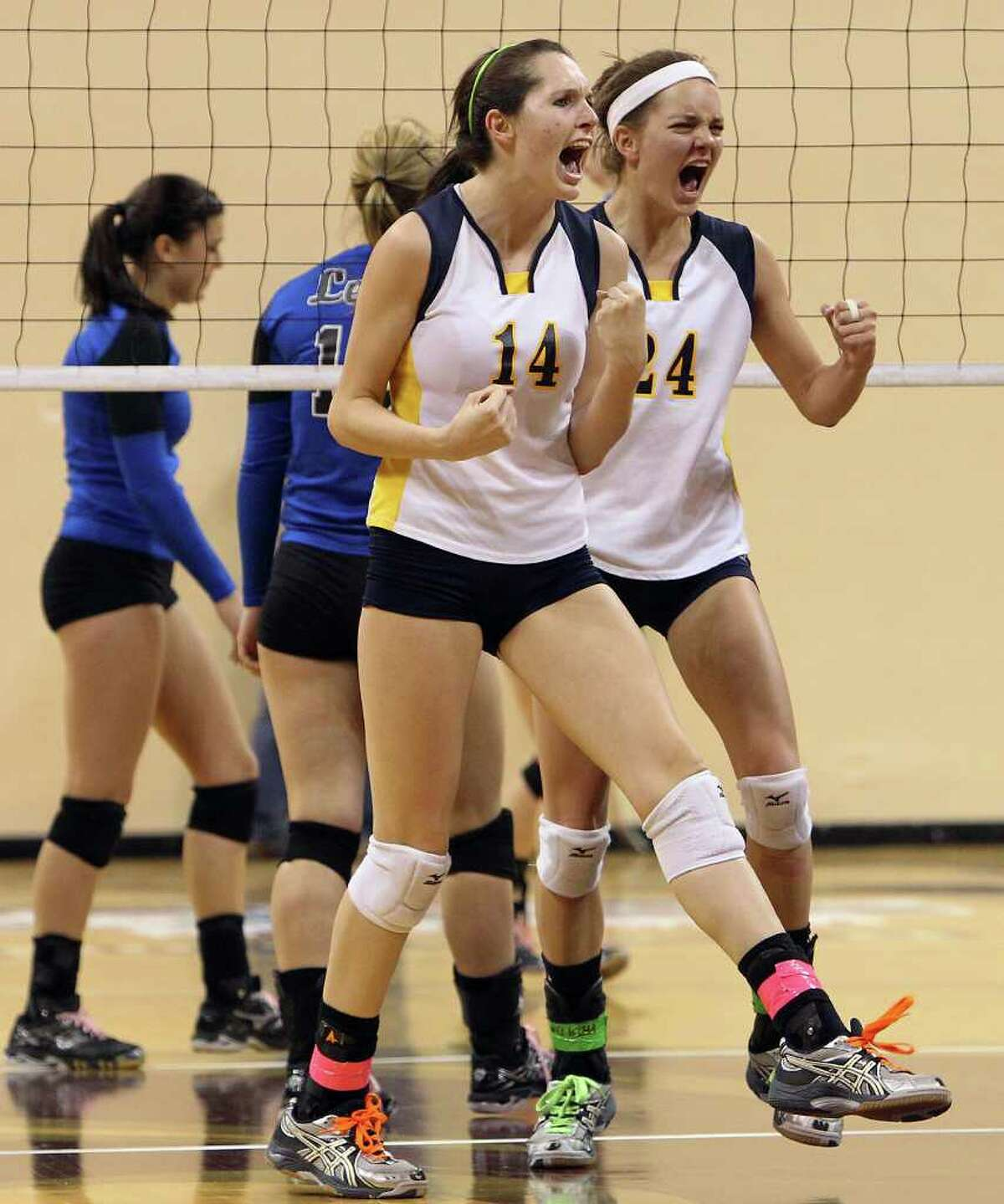 Poth's Kelsee Felux (14) and Micah Weaver (24) react after scoring against Jewett Leon in 2A State semifinal volleyball in Strahan Coliseum at Texas State University in San Marcos on Thursday, Nov. 17, 2011. Poth defeated Leon in four games to move onto the state finals to be played on Saturday.