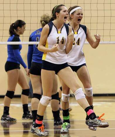 Poth's Kelsee Felux (14) and Micah Weaver (24) react after scoring against Jewett Leon in 2A State semifinal volleyball in Strahan Coliseum at Texas State University in San Marcos on Thursday, Nov. 17, 2011. Poth defeated Leon in four games to move onto the state finals to be played on Saturday. Photo: Kin Man Hui, ~ / San Antonio Express-News
