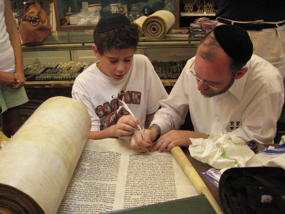 WASHINGTON JEWISH WEEK A YOUNG BOY'S GIFT: Ethan Ulanow and Rabbi Menachem Youlus restore a scroll that Ethan and his family donated to Katrina-ravaged Congregation Beth Israel. Youlus was later charged with fraud for saying the scroll (and others) was rescued from the Ukraine during the Holocaust. Photo: Photo Courtesy Washington Jewish
