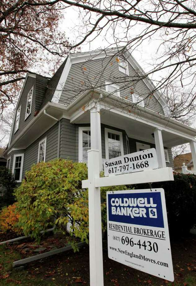 A real estate sign hangs in front of a home, in Milton, Mass., Wednesday, Nov. 16, 2011. The average rate on the 30-year mortgage stayed near 4 percent for the third straight week, just above the record low. But cheap mortgage rates have done little to boost home sales or refinancing. (AP Photo/Steven Senne) Photo: Steven Senne