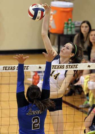 Poth's Kelsee Felux (14) extends for a kill against Jewett Leon's Chelby Stanford (02) in 2A State semifinal volleyball in Strahan Coliseum at Texas State University in San Marcos on Thursday, Nov. 17, 2011. Poth defeated Leon in four games to move onto the state finals to be played on Saturday. Photo: Kin Man Hui, ~ / San Antonio Express-News