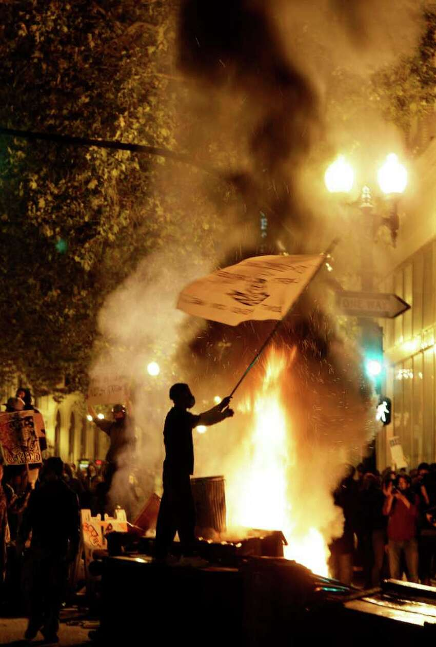 An Occupy Oakland protester waves a flag next to a bonfire in Oakland, Calif., Thursday, Nov. 3, 2011.