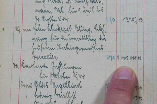 An entry in a ledger book kept by Hitler's staff of the Fuhrer's expenses shows a payment for one million marks to Helen Schwarzel, a reward paid by Adolf Hitler for information leading to the capture and subsequent executiuon of Karl Friedrich Goerdeler who Hilter considered part of a plot to depose him. Alexander's Autograph will auction off the ledger and other World War II artifacts including Adolf Hitler's desk set which was used to sign the 1938 Munich Pact between France, England, Italy and Germany that allowed Hitler to annex the Sudetenland in Czechoslovakia, a moment of infamy in European history. Also for sale are various post World War II documents showing collusion between various officials to help Nazis escape central Europe. Photo: Keelin Daly / Stamford Advocate