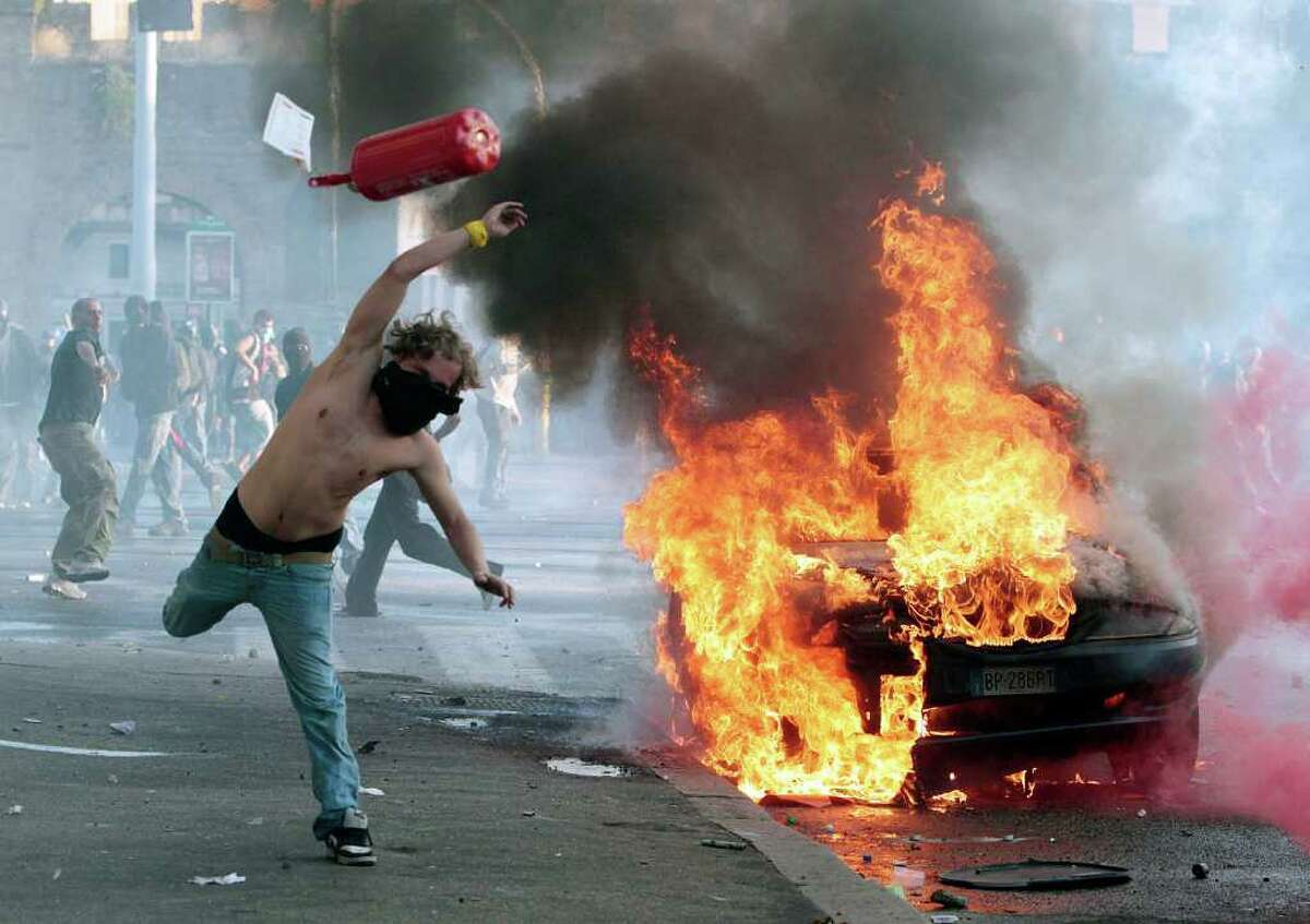 A protestor hurls a canister towards police next to a burning car during clashes in Rome, Saturday, Oct. 15, 2011. Protesters in Rome smashed shop windows and torched cars as violence broke out during a demonstration in the Italian capital, part of worldwide protests against corporate greed and austerity measures, entitled Occupy Wall Street. (AP Photo/Gregorio Borgia)