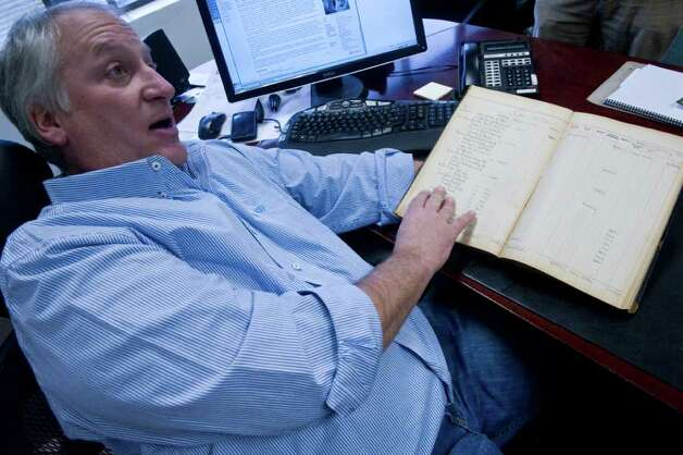 Bill Panagopulos of examines a ledger book kept by Hitler's staff of the Fuhrer's expenses in his office at Alexander's Autograph in Stamford, Conn., November 17, 2011. Alexander's Autograph will auction off the ledger and other World War II artifacts including Adolf Hitler's desk set which was used to sign the 1938 Munich Pact between France, England, Italy and Germany that allowed Hitler to annex the Sudetenland in Czechoslovakia, a moment of infamy in European history. Also for sale are various post World War II documents showing collusion between various officials to help Nazis escape central Europe. Photo: Keelin Daly / Stamford Advocate