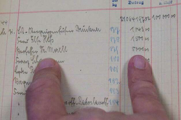 An entry in a ledger book kept by Hitler's staff of the Fuhrer's expenses shows a payment to one of Hitler's personal physician for 5,000 marks. Alexander's Autograph will auction off the ledger and other World War II artifacts including Adolf Hitler's desk set which was used to sign the 1938 Munich Pact between France, England, Italy and Germany that allowed Hitler to annex the Sudetenland in Czechoslovakia, a moment of infamy in European history. Also for sale are various post World War II documents showing collusion between various officials to help Nazis escape central Europe. Photo: Keelin Daly / Stamford Advocate