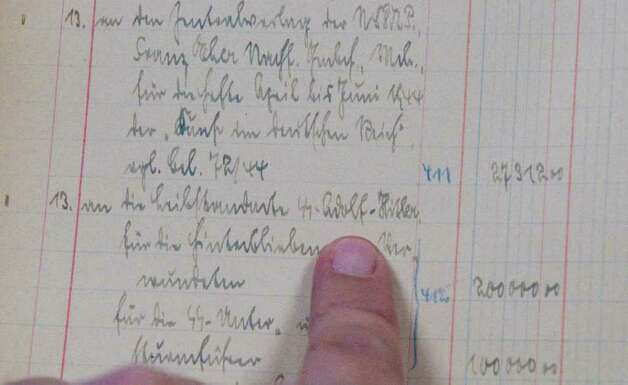 An entry in a ledger book kept by Hitler's staff of the Fuhrer's expenses shows a payment of 200,000 marks to a group of SS soldiers named for him and know to have served as his personal bodyguards. Alexander's Autograph will auction off the ledger and other World War II artifacts including Adolf Hitler's desk set which was used to sign the 1938 Munich Pact between France, England, Italy and Germany that allowed Hitler to annex the Sudetenland in Czechoslovakia, a moment of infamy in European history. Also for sale are various post World War II documents showing collusion between various officials to help Nazis escape central Europe. various officials to help Nazis escape central Europe. Photo: Keelin Daly / Stamford Advocate