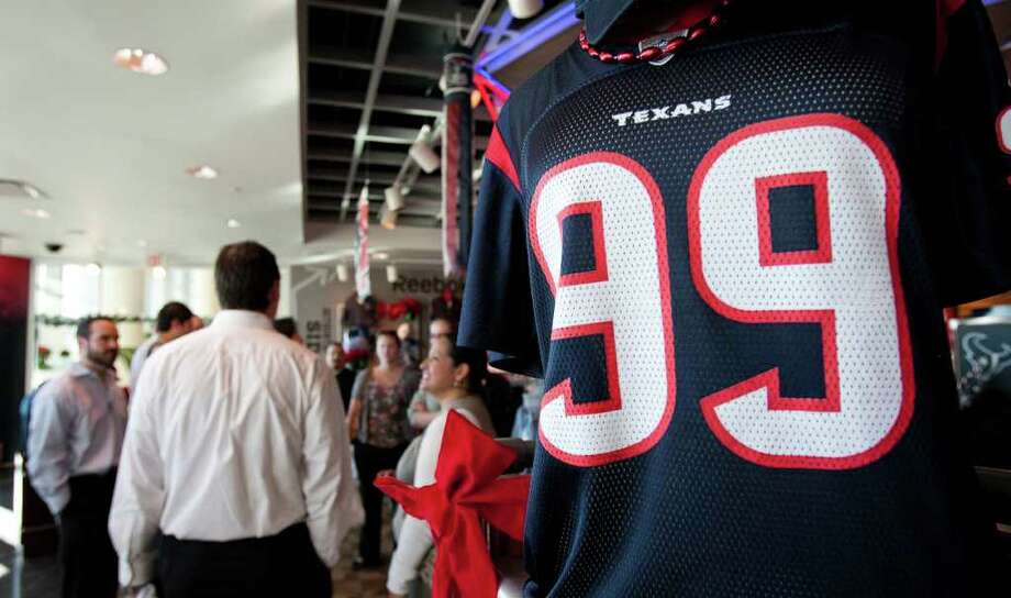 Andrew Richardson Photos : Chronicle GOOD NUMBERS: A group from Energy Architecture tours the Go Texans shop at Reliant Stadium this week. Stores that sell Texans apparel likely will set sales records if Houston reaches the playoffs. No. 99 is defensive end J.J. Watt. Photo: Andrew Richardson / © 2011 Houston Chronicle