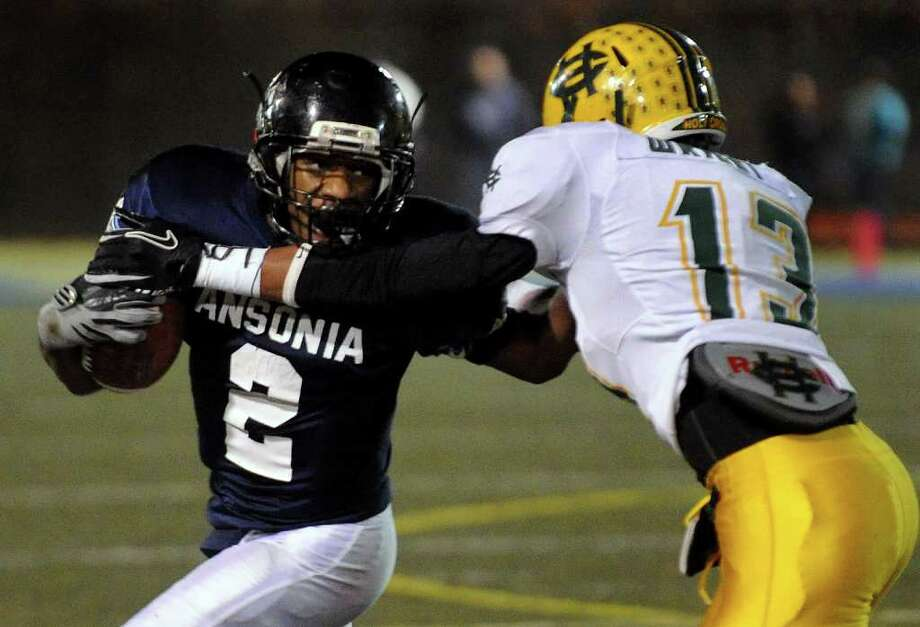 Ansonia's #2 Arkeel Newsome, left, tries to shake Holy Cross' #13 Isaiah Wright, during NVL Chapionship football action in Waterbury, Conn. on Wednesday November 17, 2011. Photo: Christian Abraham / Connecticut Post