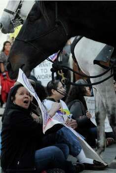 An Occupy Houston marcher reacts as a police horse grabs her poster and she stages a sit-in in the middle of the street Thursday, Nov. 17, 2011, in downtown Houston. About a dozen marchers were arrested. Photo: Pat Sullivan, Associated Press / AP