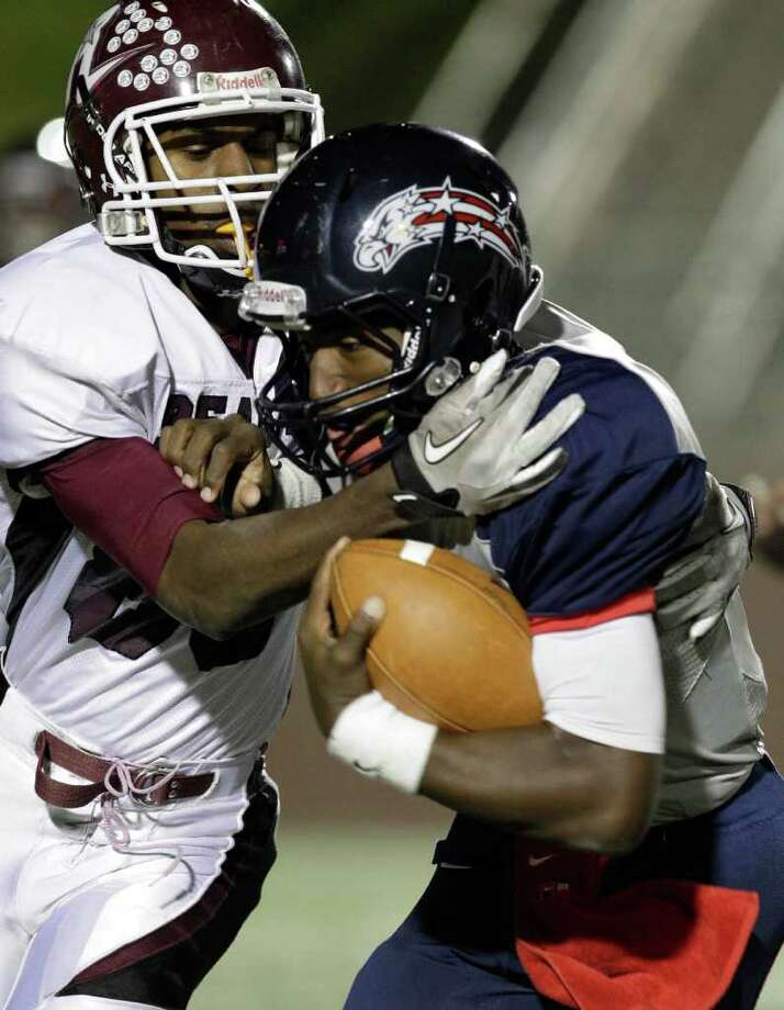 Reagan High School Dexter Rogers, left,  works to bring down Dawson High School quarterback Garry Kimble. Photo: Melissa Phillip, Houston Chronicle / © 2011 Houston Chronicle