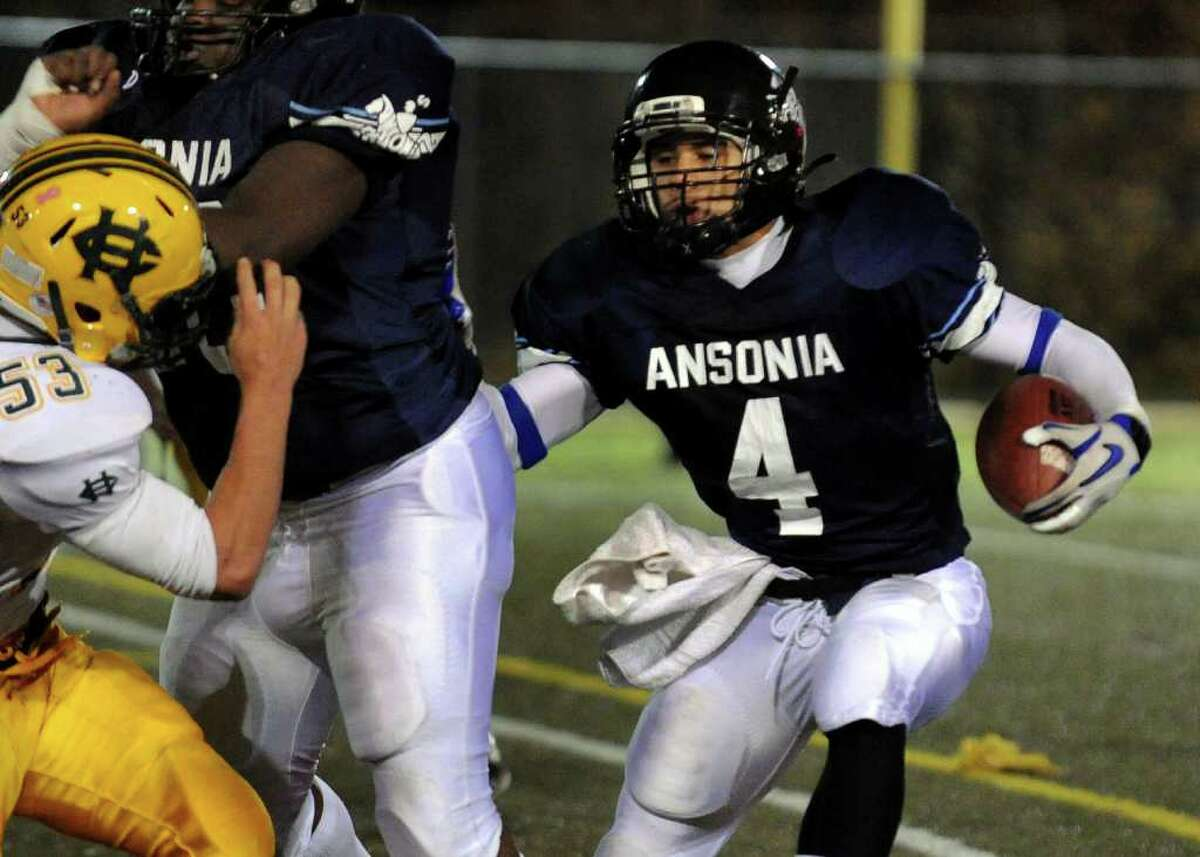 Ansonia's #4 Andrew Matos works to carry the ball , during NVL Chapionship football action in Waterbury, Conn. on Thursday November 17, 2011.