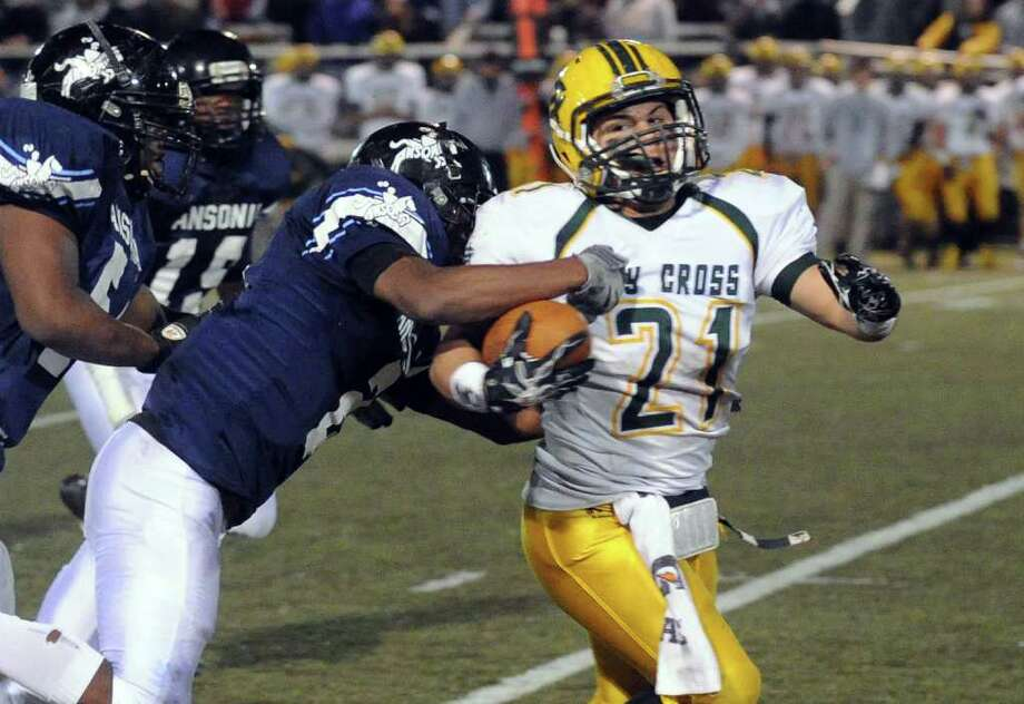 Highlights from NVL Chapionship football action between Holy Cross and Ansonia in Waterbury, Conn. on Thursday November 17, 2011. Ansonia's #2 Arkeel Newsome, left, tackles Holy Cross' #21 Dave DiGiorgi. Photo: Christian Abraham / Connecticut Post