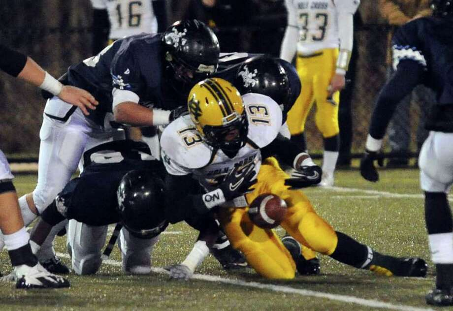 Highlights from NVL Chapionship football action between Holy Cross and Ansonia in Waterbury, Conn. on Thursday November 17, 2011. Holy Cross' #13 Isaiah Wright momentarily fumbles the ball as he is tackled. Photo: Christian Abraham / Connecticut Post