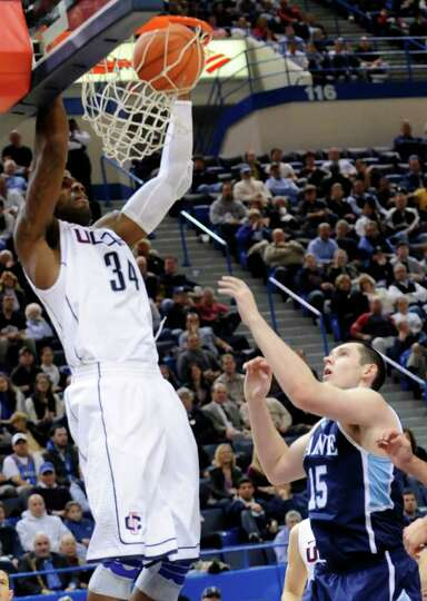 Connecticut's Alex Oriakhi dunks as Maine's Alasdair Fraser, right, watches in the second half of