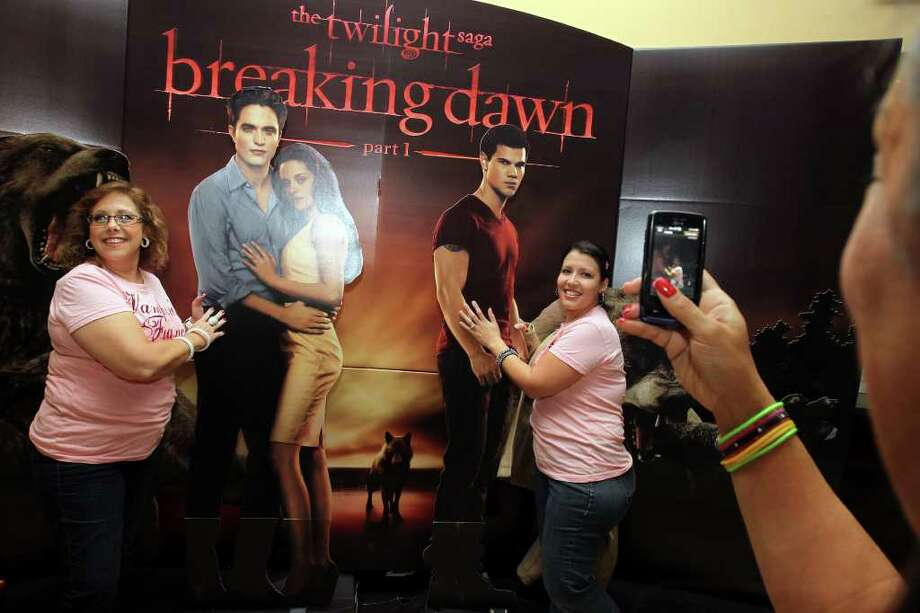 Nina Johnson, left, and her daughter, Misty Avila, pose for a friend to take a photo of them withe characters in the Twilight Breaking Dawn poster as they wait to see the opening midnight showing of Twilight Breaking Dawn at the Palladium Theatre at The RIM, Thursday, November 17, 2011. Photo: Jennifer Whitney, Jennifer Whitney/ Special To The Express-News / Jennifer Whitney/special to the Express-News