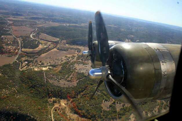 "The WWII era B-17 bomber ""Aluminum Overcast"" flies over the Texas Hill Country Wednesday near Kerrville, Texas. The plane is operated by the Experimental Aircraft Association. Photo: JOHN DAVENPORT, SAN ANTONIO EXPRESS-NEWS / SAN ANTONIO EXPRESS-NEWS (Photo can be sold to the public)"