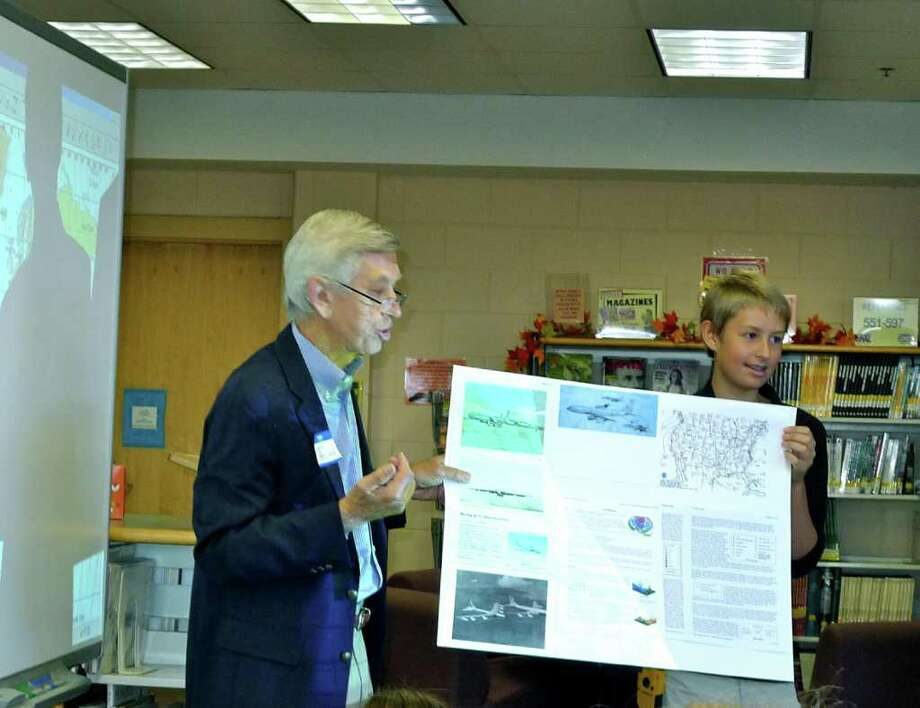John Peeling, a captain in the U.S. Air Force from 1961 to 1964, gives a presentation with seventh-grader David Wilson. Photo: Contributed Photo
